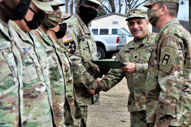 U.S. Army Lt. Col. Benjamin Kenion, commander 3-312th Training Support Battalion, Fort Meade, Maryland, and Command Sgt. Maj. Michael Lopez, senior enlisted advisor for the Battalion, congratulates Soldiers part of the battalion command staff during an awards ceremony for recognition of their hard work and dedication during the mobilization process and achieving mission readiness December 18 at Fort Hood, Texas. The unit is on a yearlong assignment to Fort Hood in support of operations for First Army Division West, 120th Infantry Brigade. (U.S. Army Reserve Photo Staff Sgt. Erick Yates)