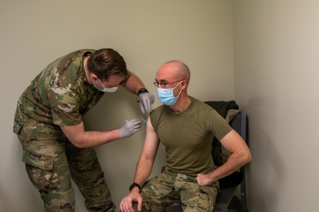 """Sgt. Jonah Prescott, combat medic, U.S. Army Medical Department Activity, Blanchfield Army Community Hospital, left, gives Maj. Benjamin Thompson, senior brigade physician assistant, C Company, 426 Brigade Support Battalion, 1st Brigade Combat Team, """"Bastogne"""", 101st Airborne Division (Air Assault), right, his first dose of the COVID-19 Pfizer BioNtech vaccination Jan. 12, at BACH on Fort Campbell, Ky. Five Soldiers from C Co., 426 BSB volunteered to receive the COVID-19 vaccination to mitigate the spread of the virus. (U.S. Army photo by Maj. Vonnie Wright, 1st Brigade Combat Team Public Affairs.)"""