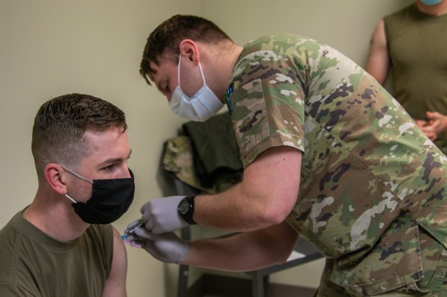 """U.S. Army Sgt. Jonah Prescott, combat medic, MEDDAC, Blanchfield Army Community Hospital, right, gives Sgt. Jacob Settles, combat medic, C Company, 426 Brigade Support Battalion, 1st Brigade Combat Team, """"Bastogne"""", 101st Airborne Division (Air Assault), left, his first dose of the COVID-19 Pfizer Biontech vaccination Jan. 12, within BACH on Fort Campbell, Ky. Five Soldiers from C Co., 426 BSB volunteered to receive the COVID-19 vaccination to mitigate the spread of the virus. (U.S. Army photo by Maj. Vonnie Wright, 1st Brigade Combat Team Public Affairs.)"""