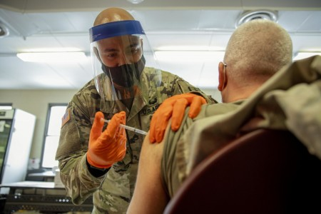 Army Staff Sgt. Nigel Chen, a New York National Guardsman, administers the Pfizer-BioNTech COVID-19 vaccine at the Camp Smith Training Site Medical Readiness Clinic, N.Y., Dec. 18, 2020. The New York National Guard is administering 44,000 doses of the Pfizer vaccine to front line medical personnel at 16 locations around the world as part of a pilot program.