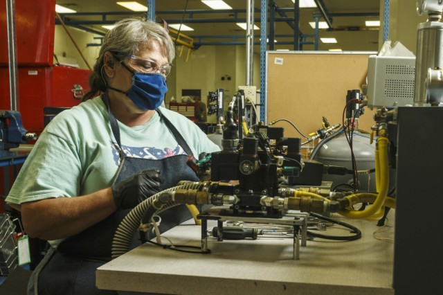 Martha Hunter, a pneudraulics mechanic at Anniston Army depot, connects a hydraulic component to a testing apparatus for a Stryker vehicle. (U.S. Army photo by Mark Cleghorn)