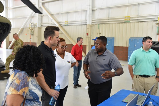 Terrence Skinner, far right, speaks with Masheldia Green, center, item manager for Chinook engines, and Dustin Spane, left, a logistics management specialist for the Chinook helicopters, about training equipment and how his team trains Soldiers in the field using a virtual program in 2018. (Photo by Preston Benson, RTC)