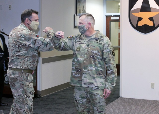 Command Sgt. Maj. Christopher Gunn (right) is greeted by Lt. Col. Kevin Taaffe of the British Army following Gunn's Relinquishment of Responsibility Ceremony on Jan. 19 at Fort Bliss, Texas. (Photo by Maj. Mike Van Kleeck / U.S. Army Joint Modernization Command)