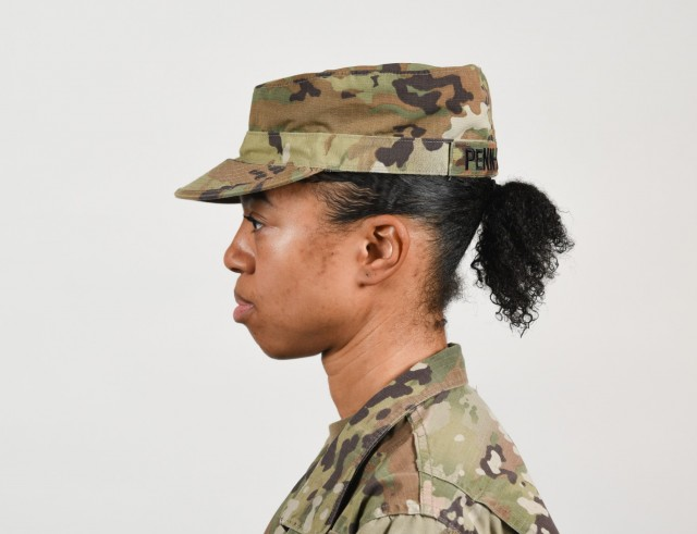 A female Soldier poses for an example photo with medium-length hair secured into a ponytail to support an upcoming change to Army grooming and appearance standards. Medium-length ponytails are only authorized for wear on the back of the scalp and cannot exceed the head's width or interfere with a Soldier's headgear.