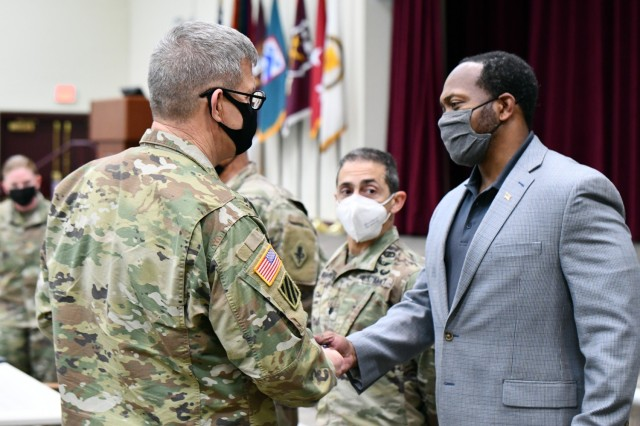 Lt. Gen. James Rainey presents a coin to Mr. Chris Fowler, Executive Officer, Office of the Deputy to the Commanding General.