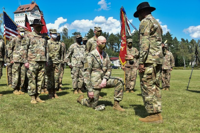 Command Sgt. Maj. Jabari O. Williams, the senior enlisted advisor of the 2nd Armored Brigade Combat Team, 3rd Infantry Division, inducts Col. Scott O'Neal, outgoing commander of the 2ABCT, to the Order of St. George on Tower Barracks Parade Field, Grafenwöhr, Germany July 20. To be inducted, among other requirements, you must be a platoon sergeant, or above, and demonstrate outstanding leadership, technical and tactical competence, and exceptional teamwork while serving specifically in Armor and Cavalry units. (U.S. Army photo by Spc. Javon Johnson/ 7th Army Training Command)