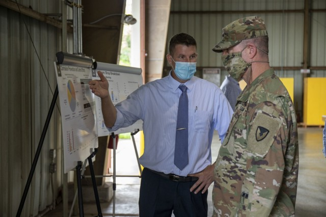 The 402nd Army Field Support Battalion-Hawaii's Sean Mager briefs Army Sustainment Command's commanding general Maj. Gen. Daniel Mitchell on their corrosion prevention and repair program.