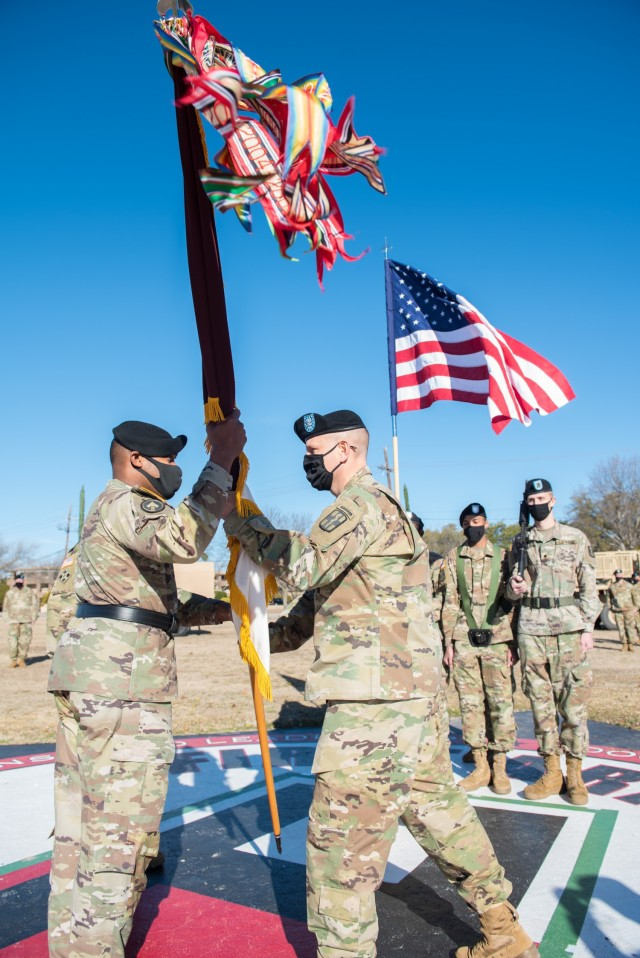 Col. Robert F. Howe II, the outgoing 1st Med. Bde. Commander, passes the guidon to the 13th Expeditionary Sustainment Command's Commanding General, Brig. Gen. Ronald R. Ragin Jan. 14.  During a change-of-command ceremony, the transfer of the guidon signals the relinquishment of command to the new commander. (U.S. Army photo by Sgt. 1st Class Kelvin Ringold)