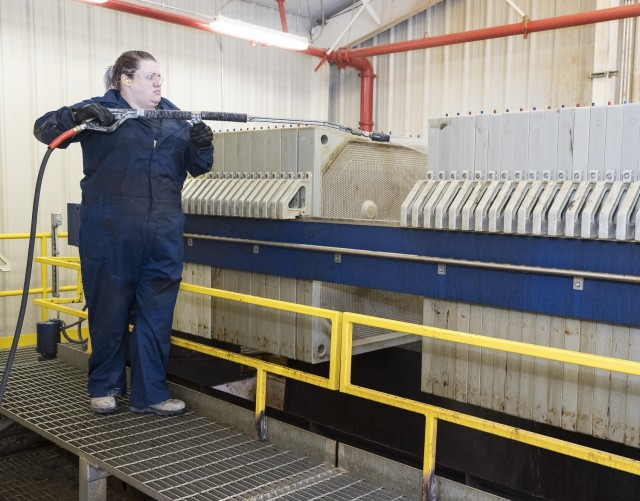 Kayla French, a waste water treatment plant operator, press washes filter plates before replacement with new ones.  French, along with teammates in DPW and DPE, worked during the holiday period to perform preventive maintenance on the depot's equipment and machinery.