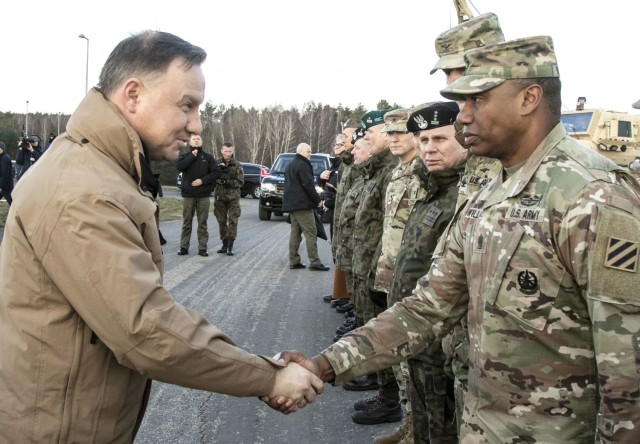 Command Sgt. Maj. Jabari Williams(Right), the senior enlisted advisor of the 2nd Armored Brigade Combat Team, 3rd Infantry Division, greets Andrzej Duda(Left), President of the Republic of Poland during a troop engagement event on Bucierz Range at Drawsko Pomorskie Training Area, Poland, in support of DEFENDER-Europe 20, March 11, 2020. (U.S. Army photo by Staff Sgt. Brian K. Ragin Jr.)