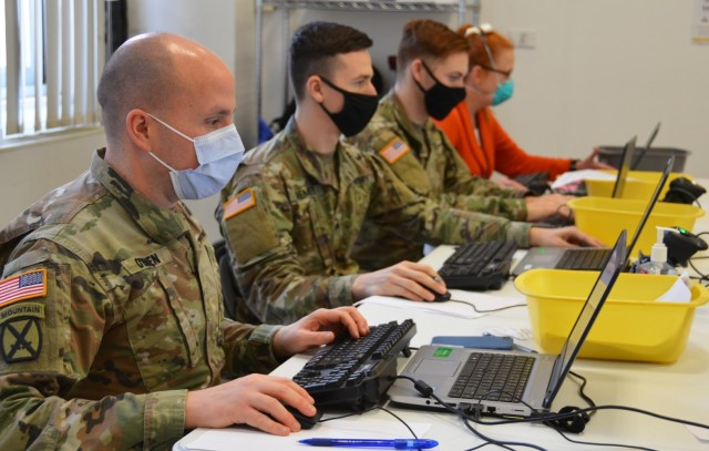 U.S. Army Health Center Vicenza Pharmacy Officer in Charge Maj. Sean O'Brien (left) and other staff members check reservations made for flu vaccinations Jan. 15, 2021, on Caserma Ederle. More than 1,000 people signed up to receive their flu shot during the campaign.