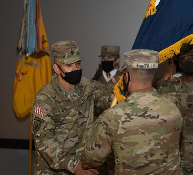 Col. Terry R. Tillis, the commander of 2nd Armored Brigade Combat Team, 3rd Infantry Division, passes the brigade colors to incoming senior enlisted advisor Command Sgt. Maj. Jaime Lopez during a change of responsibility ceremony, Jan. 22, 2021, at Woodruff Theater on Fort Stewart, Georgia. The ceremony marks the official transition of responsibility from Command Sgt. Maj. Jabori O. Williams to Command Sgt. Maj. Lopez. (U.S. Army photo by Spc. Devron Bost)