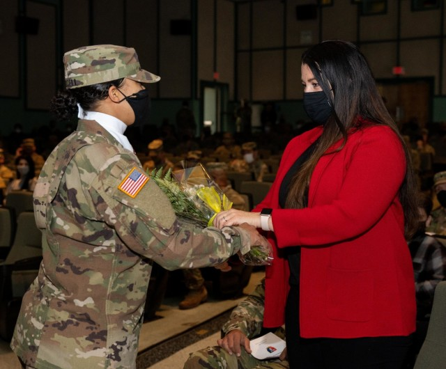 Kory Lopez, wife of incoming senior enlisted advisor, Command Sgt. Maj. Jaime Lopez receives yellow roses to welcome her into the Spartan Brigade family during a 2nd Armored Brigade Combat Team, 3rd Infantry Division, change of responsibility ceremony, Jan. 22, 2021, at Woodruff Theater on Fort Stewart, Georgia. (U.S. Army photo by Spc. Devron Bost)
