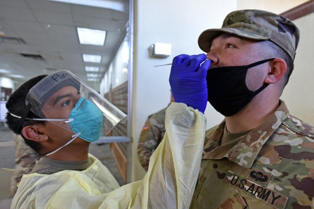 Pvt. Daniel Flores with Alpha Company, 232nd Medical Battalion, uses a cotton swap to test Staff Sgt. Jose Gomez with Alpha Company 264th Medical Battalion for COVID-19.