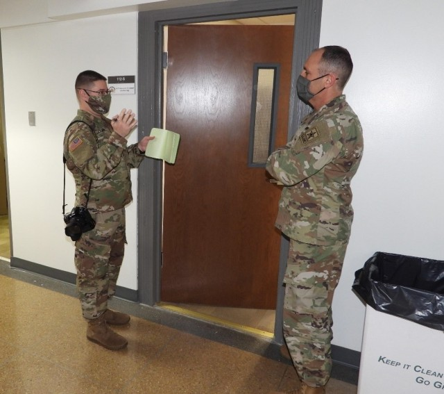 Staff Sgt. Dmitriy Arkannikov, team member with the 126th Military History Detachment, speaks with Col. Anthony Hammett, G-9, National Guard Bureau, about potential interviews during the 59th Presidential Inauguration in Washington, D.C., January 17, 2021. They are among the more than 25,000 National Guardsmen supporting the 59th Presidential Inauguration event.