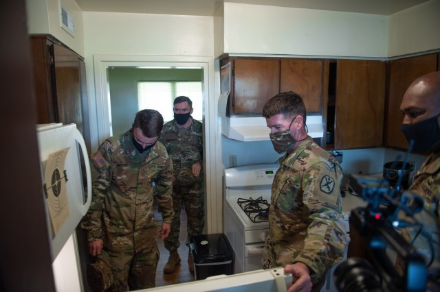 """FORT BENNING, Ga. – Maj. Gen. Patrick J. Donahoe, commanding general of the U.S. Army Maneuver Center of Excellence and Fort Benning, gets a look inside a home Jan. 20 at the Norton Court residential housing area here, built in 1957. Accompanied by Command Sgt. Maj. Derrick C. Garner (right), MCoE's senior enlisted leader, and other key officials, Donahoe made the visit as part of a new program of """"walking town hall"""" visits to the post's housing areas. The visits afford leaders a chance at in-person conversation with residents and a first-hand look at conditions. As a result of the visit, officials intend to schedule Norton Court for power-washing of the buildings and other improvements. Plans call for Donahoe and others to visit residential housing areas at a rate of one a month.(U.S. Army photo by Patrick A. Albright, Maneuver Center of Excellence and Fort Benning Public Affairs)"""