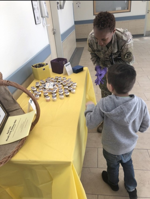 Capt. Ashley Jefferson-Watts, a clinical nurse and officer in charge of the primary care clinic at U.S. Army Health Clinic Grafenwoehr, hands out gifts to a child during a Month of the Military Child event in April 2020.