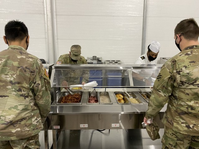 Sgt. 1st Class Alechia Riley (right), dining facility manager with 3rd Infantry Division serves Soldiers breakfast during the grand opening of the temporary dining facility Jan. 21. This temporary facility will be open while the permanent facility receives a modernization remodel.