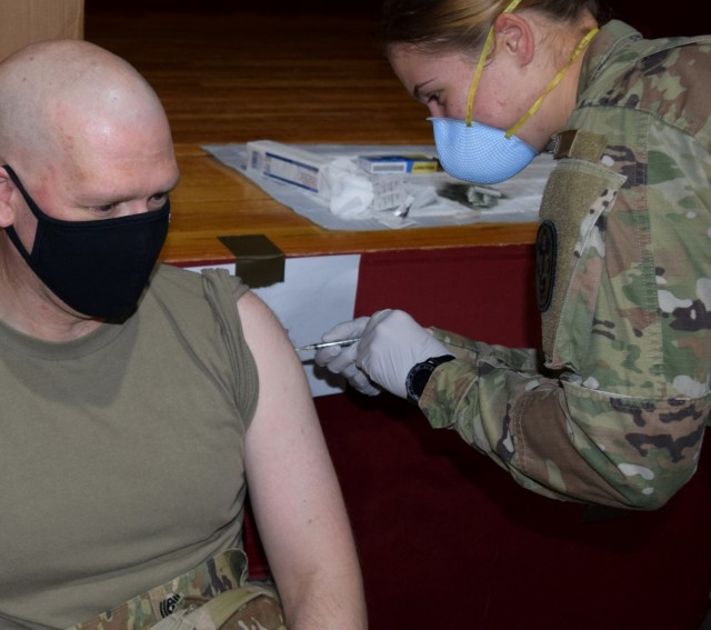 Command Sgt. Major Christopher Prosser receives his booster shot of the COVID-19 vaccine at the hands of Specialist Anna Hatchett, a medic assigned to the McAfee U.S. Army Health Clinic at White Sands Missile Range, N.M.