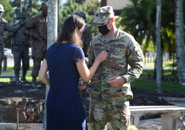 """Andrea Gaspard, wife of Col. Joshua Gaspard, G3 operations officer, 25th Infantry Division, removes the rank of lieutenant colonel from her husband's chest during his promotion ceremony, on Schofield Barracks, Hawaii, Nov. 13, 2020. Gaspard, promoted to colonel, is one of the first officers in the U.S. Army to get a brevet promotion in over 100 years. """"I think when you look at it, from all the lenses, I have had phenomenal bosses and leadership throughout the years, and I can say without a doubt I have never been in a bad unit,"""" said Gaspard. """"I have no bad stories. What I will tell you is really, my wife Andrea, she's a mother of four, graduated from West Point, she went back to school and got her nursing degree, nurse practitioners degree, and her doctorate in nursing practice. To see what she does and always putting our children first, it's all pretty inspiring."""""""