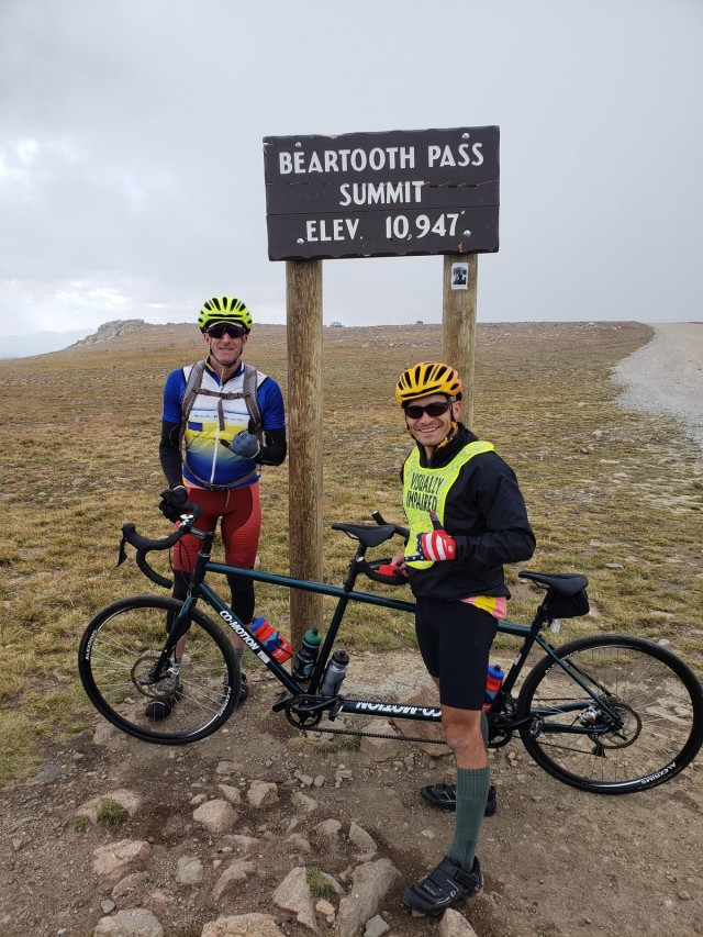 Staff Sgt. Mike Murphy (right) and Marc Cattapan (left) pose in front of the Beartooth Pass sign, the highest point in the Beartooth Challenge ride. (Photo via Marc Cattapan)