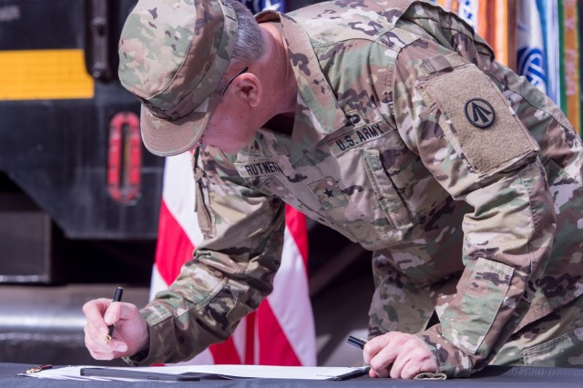 U.S. Army Brigadier General Stephen Rutner, commander of Deployment Support Command, signs the Memorandum of Agreement at Joint Base Langley-Eustis, Virginia, Nov. 6, 2020. The MOA allows Soldiers of the 757th Transportation Battalion, a reserve unit, the opportunity to complete active duty time and more career broadening options. (U.S. Air Force photo by Senior Airman Derek Seifert)