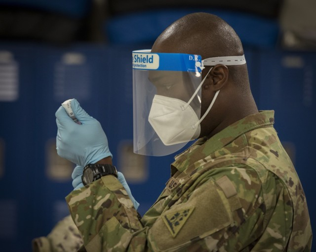 U.S. Army Staff Sgt. Donnell Niles, 192nd Engineer Battalion combat medic, draws Moderna COVID-19 vaccine from a vial into a syringe at Bradley Air National Guard Base in East Granby, Connecticut, Jan. 2, 2021. The Connecticut National Guard began administering the vaccine in accordance with the Department of Defense COVID-19 Vaccine Distribution Plan, with doses voluntarily administered to Soldiers and Airmen on the front lines of the COVID-19 pandemic response. (U.S. Air National Guard photo by Staff Sgt. Steven Tucker)