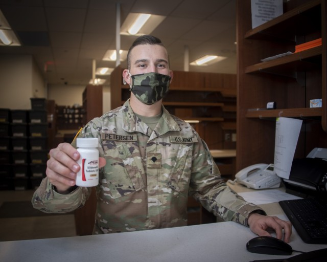 Army Spc. John Petersen, pharmacy technician, hands a prescription to a beneficiary at the Community Pharmacy in the Exchange, Fort Sam Houston, Texas, Feb. 1, 2021. On average, new prescriptions take about 30 minutes to fill. For prescription refills customers generally wait about 2 minutes for pick up. (U.S. Army photo by Jason W. Edwards)