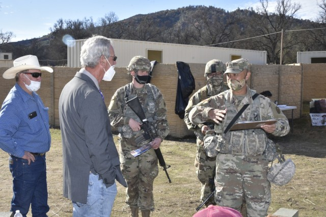 """80th Training Command's TASS Psychological Operation (PSYOP) students at Fort Hunter Liggett, California patronize the village """"market"""" as they also discover information and combat misinformation via flyers posted in the village. Role players stay in character during the seven-day field training, providing Soldiers and Marines with real life scenarios of the type they may be faced with some day. Army Reserve Soldiers (L to R): Spc. Nathan Moore, 1005 PSYOP/Civil Affairs Training Co., Marina, California; Spc. Angel Esquivel, 393rd Tactical PSYOP Co., Arlington Heights, Illinois; and Sgt. 1st Class Kris Kaopuiki, 25th Infantry Division Main Command Post Operational Detachment, Schofield Barracks, Hawaii."""