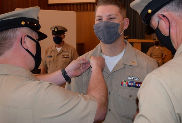 A mask can't hide the smile of Dylan Munn as fellow Sailor pin on his golden anchors signifying his promotion to chief petty officer on Jan. 29, 2021, at White Sands Missile Range, N.M.