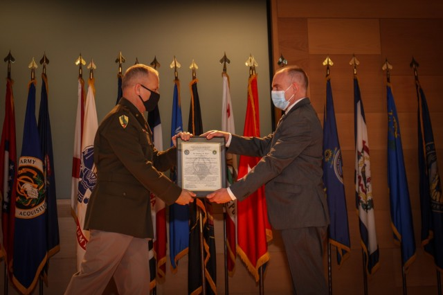 Brig. Gen. Robert M. Collins hands the charter for Project Manager Interoperability, Integration and Services to incoming Project Manager, Matthew Maier. The ceremony marked the organization's transition from Project Lead to Project Manager.