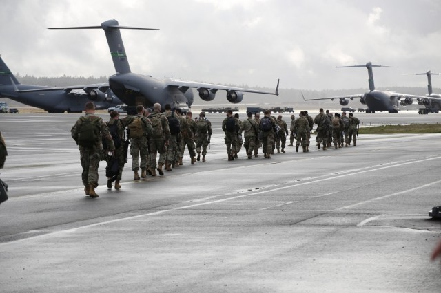 Washington National Guard members leave the McChord Field passenger terminal and walk to an awaiting KC-135 to head to D.C. to support Operation Capitol Response Jan. 15, 2021, at Joint Base Lewis-McChord, Wash. The 141st Air Refueling Wing flew seven KC-135s that transported over 300 Washington Guardsmen and over 34,000 pounds of cargo in support of the 59th Presidential Inauguration. (U.S. Army National Guard photo by Joseph Siemandel)
