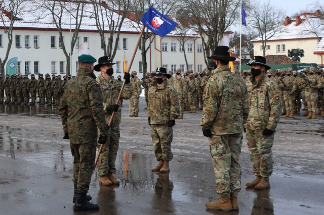 United States Army Lt. Colonel Jason Adler, 1st Squadron, 2d Cavalry Regiment, holds the flag he received from Jeffery Higgins, 2d Squadron, 2d Cavalry Regiment signifying that Adler is the new NATO enhanced Forward Presence Battle Group Poland Commander. (Photo courtesy of eFP BGP PAO)