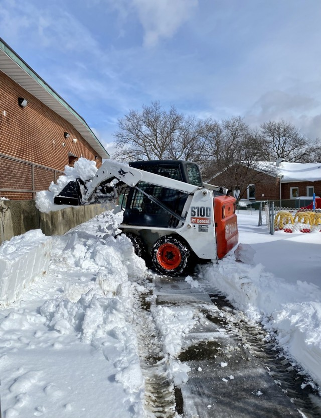 A skid steer clears snow out of the Child Development Center area on Fort Hamilton, N.Y., Feb. 3, 2021. A major winter storm struck the Mid-Atlantic and Northeast, creating near-blizzard conditions along the coast, forcing many to stay home and telework.  Despite the conditions, essential members of the garrison staff came together and persevered through the snow, sleet, wind, and power outage in order to ensure the safety and convenience of the installation's residents and workforce. (U.S. Army photo by Connie Dillon)