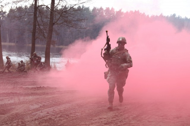 U.S. Army Second Squadron, Second Cavalry Regiment Troops emerge from the smoke ready to fight and secure a landing zone after being transported in their Strykers across a lake by the Polish Army during Tumak 20 Nov. 25, 2020, near Bemowo Piskie Training Area, Poland. (U.S. Army photo by Staff Sgt. Elizabeth O. Bryson