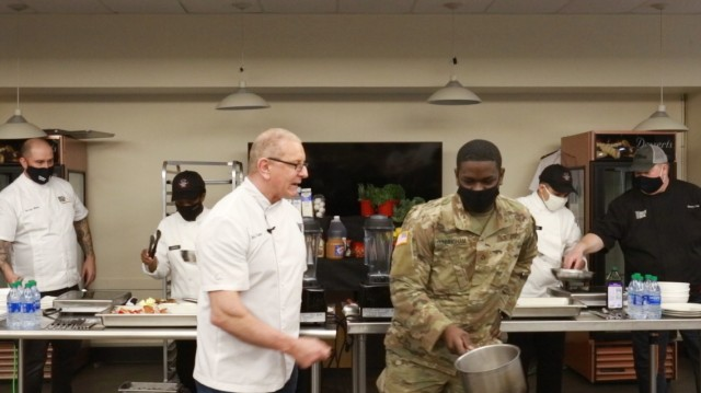 Chef Robert Irvine demonstrates proper cooking techniques with culinary specialists from the 1-2 Stryker Brigade Combat Team during a cooking demonstration at the Ghost Inn warrior restaurant on Joint Base Lewis-McChord, Washington, Jan. 25, 2021. (U.S. Army photo by Spc. Richard Carlisi.)