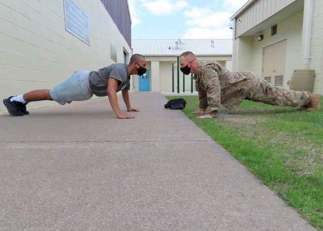 Sgt. Jason Pope conducts push-ups with a candidate during the acclimation phase at the Texas ChalleNGe Academy in Eagle Lake, Texas. The Texas National Guard Joint Counterdrug Task Force has supported the Texas ChalleNGe Academy for more than 20 years with mentorship, process improvement and training to help students succeed.