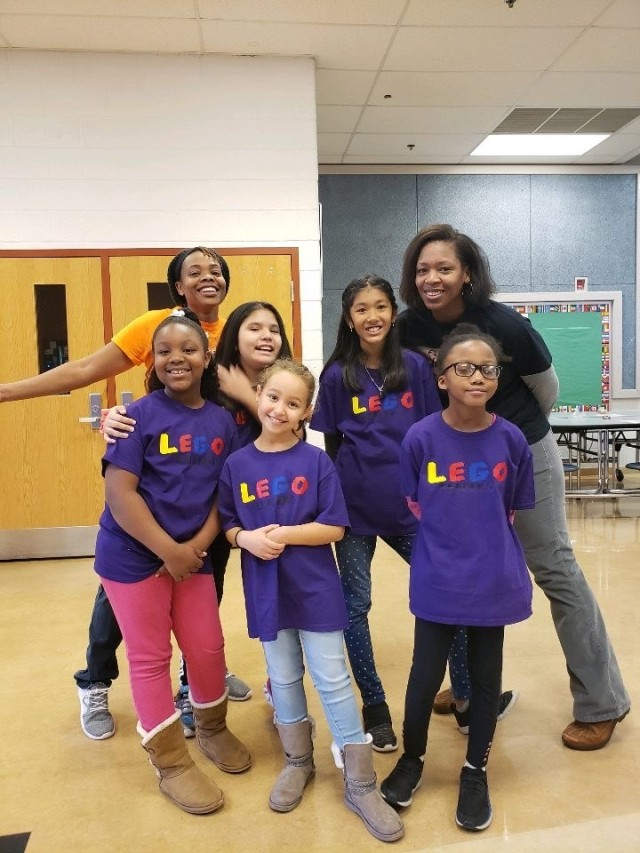 Yasmeen Neal (left) poses with mentees of a youth non-profit organization focused on robotics.