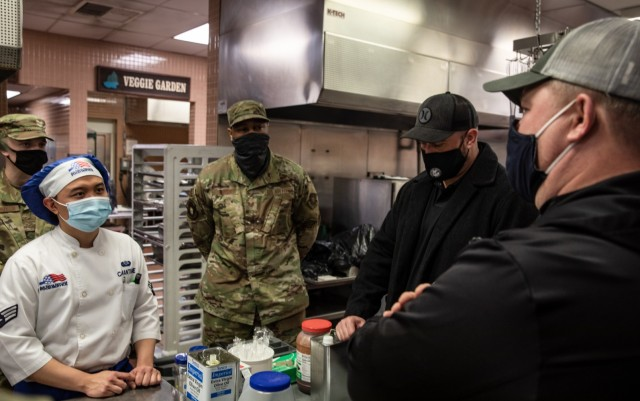 Senior Airman Charles Reynold Camantigue, a culinary specialist with the 627th Force Support Squadron, receives cooking advice from Chef Shane Cash, Chef Irvine's corporate chef and vice president of concept development, at the Olympic warrior restaurant on Joint Base Lewis-McChord, Washington, Jan. 29, 2021. (U.S. Army photo by Spc. Richard Carlisi.)
