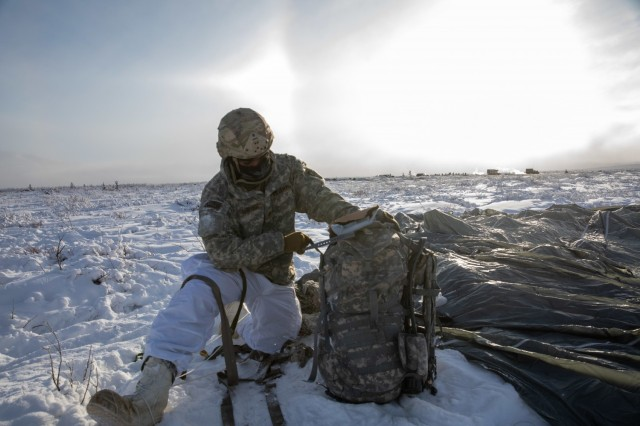 Sgt. Darnel Sawyer, a paratrooper with 3rd Battalion, 509th parachute infantry regiment, 4th Infantry Brigade Combat Team (Airborne), 25th Infantry Division, gathers his equipment after parachuting onto an airfield at Donnelley Training Area, Alaska, Feb., 08, 2021. Sawyer and approximately 500 paratroopers will spend more than a week conducting Arctic warrior 21, a near-peer combat scenario that takes place in an Arctic environment. (U.S. Army photograph by Staff Sgt. Alex Skripnichuk)