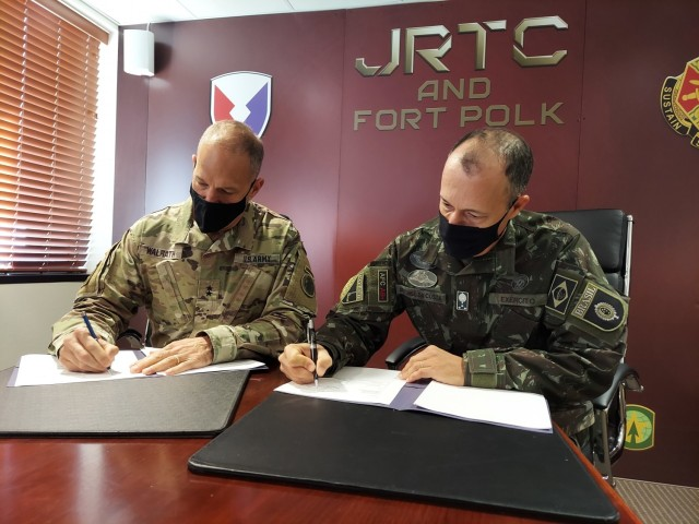 Maj. Gen. Daniel R. Walrath, Army South commanding general, left, and Lt. Gen. Marcos de Sá Affonso da Costa, chief of training, Land Forces Training Command, Exército Brasileiro, signs a technical arrangement between the Brazilian Army and the U.S. Army as represented by Army South concerning Brazilian participation in combined training exercise in conjunction with Joint Readiness Training Center Rotation 21-04 at Fort Polk, Louisiana, Feb. 1.