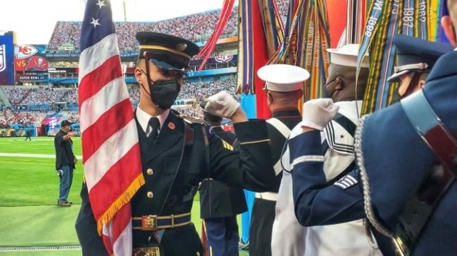 U.S. Army Sgt. Ryan Weber, bearing the National Colors, walks the line wishing his colors team luck just prior to taking the field at Super Bowl LV in Tampa, Florida, Feb. 7, 2021. The U.S. Armed Forces Color Guard is comprised of service members from the ceremonial guard units stationed in and around Washington, D.C.