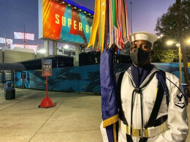 U.S. Navy Petty Officer 3rd Class James Hunter stands with the U.S. Navy service flag just after the color team's performance at Super Bowl LV in Tampa, Florida, Feb. 7, 2021. The U.S. Armed Forces Color Guard is comprised of service members from the ceremonial guard units stationed in and around Washington, D.C.