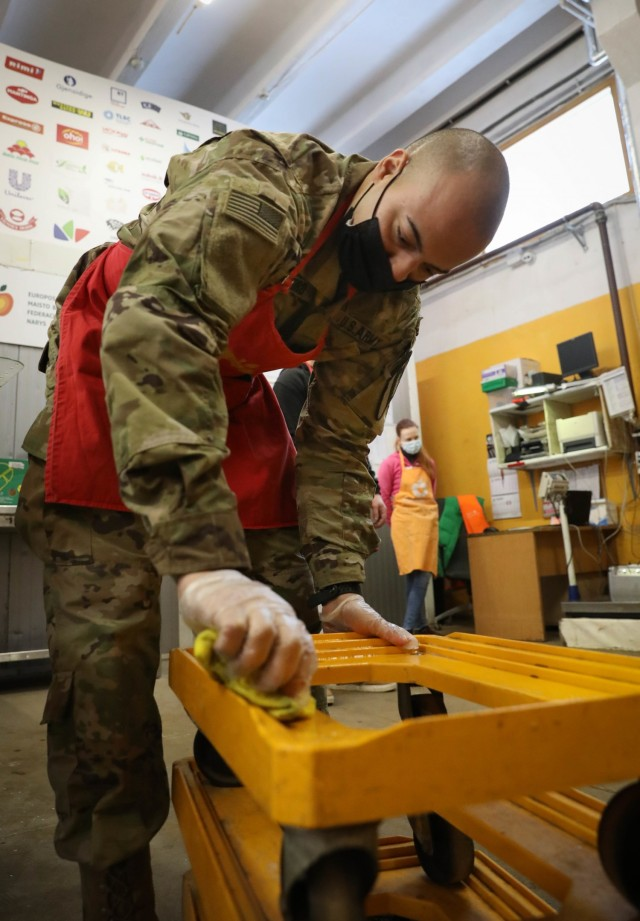 Capt. Spenser Swafford, 2nd Battalion, 8th Cavalry Regiment fire support officer and officer in charge of the Non-Lethal Fires Team, cleans a wheeled rack at a food bank in Vilnius, Lithuania, on Feb. 4, 2021. Swafford is a part of rotation U.S. forces stationed at the Pabrade Training Area and traveled to the capitol city to volunteer his time to help end food waste and end hunger. Along with cleaning, Swafford also helped create 100 food parcels that will be distributed to local citizens that are unable to shop for groceries of their own or can not afford to shop for groceries. (U.S. Army photo by Sgt. Alexandra Shea)