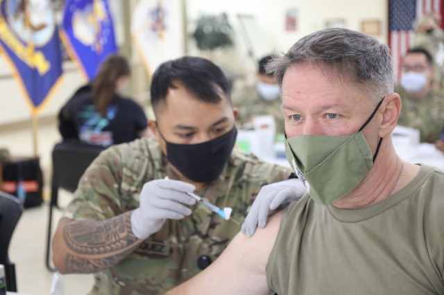 Spc. Vincebryan Marquez, healthcare specialist, 228th Combat Support Hospital, administers the Moderna COVID-19 vaccine to Lt. Col. Scott Gadberry, anesthesiologist, 228th Combat Support Hospital, at Camp Arifjan, Kuwait, Jan. 18, 2021. Camp Arifjan is utilizing a phased distribution of the vaccine, as specified by the Department of Defense, beginning with medical personnel and first responders. (U.S. Army photo by Sgt. 1st Class Noel Gerig, 1st TSC Public Affairs)