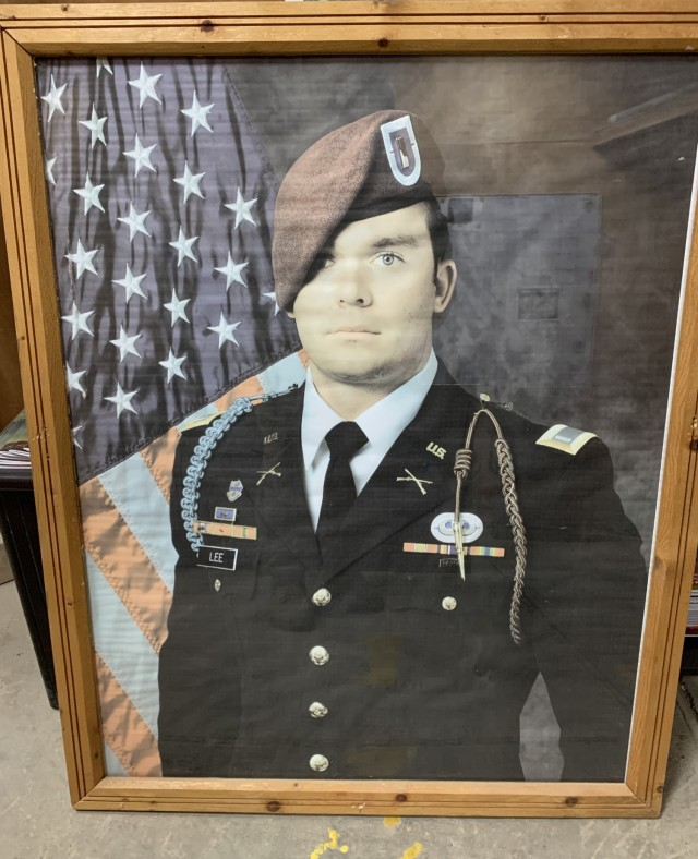 A portrait of U.S. Army 1st Lt. Weston Lee previously hung in the fieldhouse at Camp Taji, Iraq in honor of his sacrifice when he was killed in action in 2017. As the base undergoes transfer to the Iraqi forces, Lee's portrait was among the memorials that were secured or sanitized before U.S. forces leave the base. (U.S. Army photo by Chaplain (Capt.) Joel Reynolds, 168th Military Police Battalion, Tennessee Army National Guard, Combined Joint Task Force – Operation Inherent Resolve)