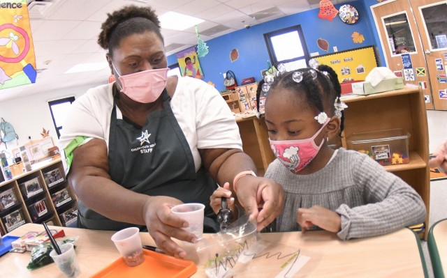 Strong Beginnings Program Assistant Judy Jones works with Madison Easter during a holiday craft-making activity in December at Fort Lee's Battle Drive Child Development Center. It was recently announced that the Child and Youth Services program here had been awarded DOD certification, an acknowledgement that it meets the department's stringent training, health and safety standards for providing military childcare. (U.S. Army Photo by T. Anthony Bell)