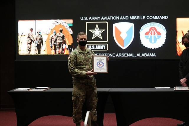 U.S. Army Aviation and Missile Command Commanding General Maj. Gen. Todd Royar displays one of the plaques presented to awardees during the Value Engineering/ Army Working Capital Fund Investment Program Awards Ceremony Feb. 8 at Bob Jones Auditorium at Redstone Arsenal, Alabama.