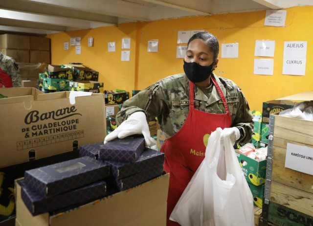 Spc. Daria Jackson, a 319th Mobile Public Affairs Detachment mass communication specialist attached to 2nd Battalion, 8th Cavalry Regiment, grabs a box of dates to fill one of 100 food parcels Feb. 4, 2021, at a Vilnius, Lithuania, food bank. Currently on a rotation at the Pabrade Training Area, Jackson volunteered about five hours of her day to help end food waste and end hunger in the capitol city. (U.S. Army photo by Sgt. Alexandra Shea)