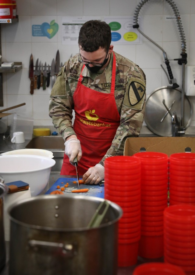 "Spc. Austin Edwards, a Trooper assigned to 2nd Battalion, 8th Cavalry Regiment, cuts carrots to add to soup Feb. 4, 2021, at a food bank in the capitol city of Vilnius, Lithuania. Edwards helped transform fruit and vegetables that were not able to be sold at local grocery stores, from ""ugly food"" to a soup that was distributed to the local homeless population. He volunteered about five hours of his day to help two kitchen staff who make about 650 meals per week. (U.S. Army photo by Sgt. Alexandra Shea)"